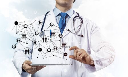 Horizontal shot of professional young doctor in white medical suit presenting social network structure above tablet in hands while standing against cloudy skyscape view on background.
