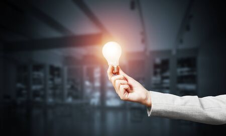 Business woman hand with glowing incandescent lamp on dark office background. Successful business solution concept with electric light bulb. Leadership and motivation. Education and knowledges 스톡 콘텐츠