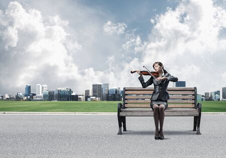 Young woman with violin sitting on wooden bench. Attractive businesslady playing violin on background modern cityline panorama in sunny day. Musician practicing and performing outdoors.