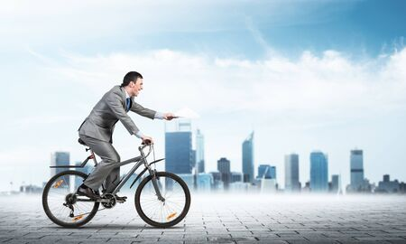 Businessman with paper documents in hand on bike. Courier with documents. Corporate employee in grey business suit riding bicycle on background of modern cityscape. Accounting and financial statements Фото со стока