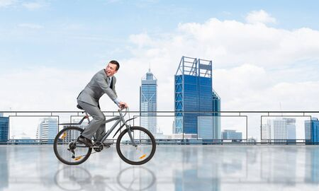 Man wearing business suit riding bicycle on penthouse balcony. Handsome cyclist looking back on background of urban architecture. Terrace with modern city center view. Outdoor fun and activity. 版權商用圖片