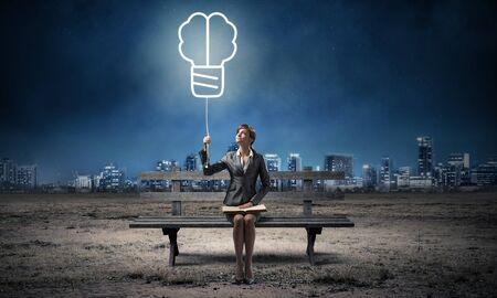 Young woman with open book on wooden bench outdoor. Business education and idea generation. Beautiful girl holding at light bulb illuminated symbol in night sky. Modern cityscape panorama at night.