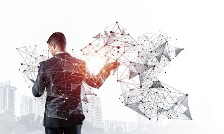 Businessman with documents pointing on abstract network with polygonal shapes. Back view of standing entrepreneur in business suit and tie. Professional business assistance and consulting service.