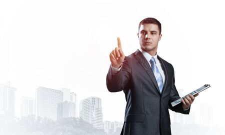 Handsome businessman standing and finger pointing at something. Front view of man in business suit and tie on background foggy cityscape. Successful business person in formal wear with raised hand Banco de Imagens