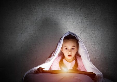 Scared little girl reading book in bed before going to sleep. Pretty child with flashlight hiding under blanket. Kid can not sleep at night. Portrait of girl in pajamas on background of grey wall. Imagens