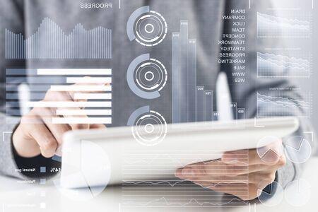 Homme d'affaires analysant les données financières. Interface virtuelle 3d au-dessus de l'écran de l'ordinateur tablette. Diagrammes financiers interactifs et visualisation de données numériques. Technologie intelligente moderne dans les processus d'affaires