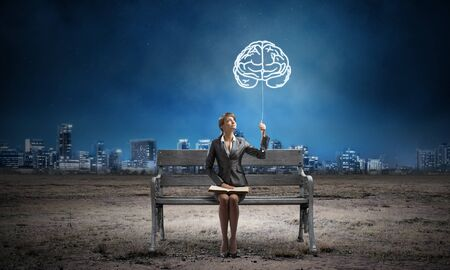 Young woman with open book sitting on wooden bench outdoor. Brainstorming and idea generation. Beautiful girl holding human brain symbol in night sky. Modern cityscape panorama at night.