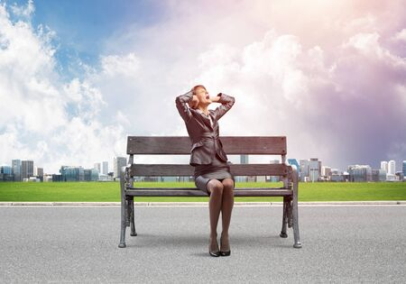 Stressful woman sitting on wooden bench. Emotional screaming girl keeps hands on head. Businesswoman in despair on background modern cityline panorama in sunny day. Woman call for help.