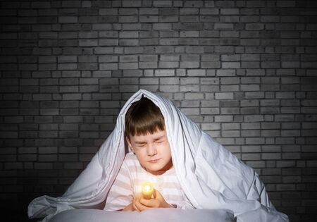Frightened child with flashlight hiding under blanket. Scared kid with closed eyes lying in bed at home. Little boy can not sleep at night. Portrait of boy in pajamas on background of brick wall