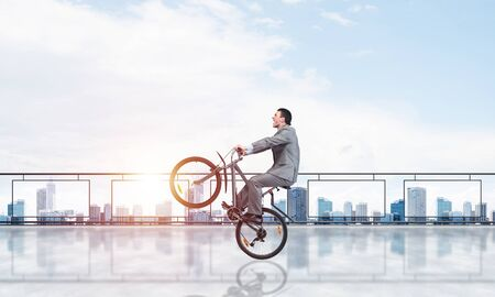 Man wearing business suit riding bicycle on penthouse balcony. Handsome cyclist popped wheelie on background of high office buildings. Terrace with modern downtown view. Outdoor fun and activity Stock Photo