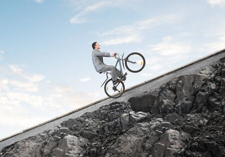 Businessman riding uphill by bike. Nature landscape with copy space. Man in business suit riding bicycle on mountain road. Cyclist popped wheelie on background of blue sky. Healthy lifestyle