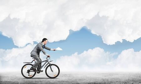Businessman with paper documents in hand on bike. Deadline for paperwork. Corporate employee in grey business suit riding bicycle on background of skyscape. Accounting and financial statements Фото со стока