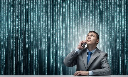 Young man talking on phone and looking upward. Businessman sitting at desk on background abstract binary code chain. Portrait of guy wears business suit and tie. Deep cyberspace and virtual network