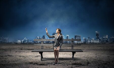 Business woman holding smartphone with raised hand. Attractive girl showing mobile phone screen on wooden bench. Mobile marketing and communication. Modern cityline panorama at night.
