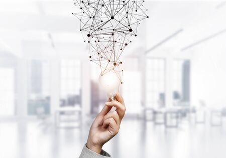 Human hand with glowing lamp and abstract digital network on blurred office background. Professional business assistance and consulting service. Successful solution business motivation with light bulb