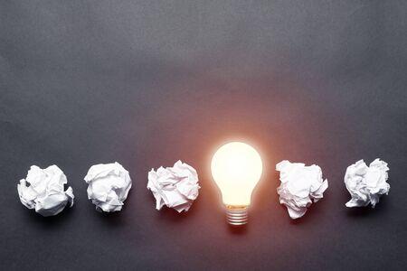 Lampadina e palline di carta bianca sgualcite su sfondo nero. Soluzione riuscita del problema. Pensa fuori dagli schemi. Motivazione aziendale con copia spazio. Idea geniale tra la metafora delle idee fallite.