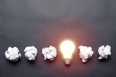 Lightbulb and crumpled white paper balls on black background. Successful solution of problem. Think outside the box. Business motivation with copy space. Genius idea among failing ideas metaphor.