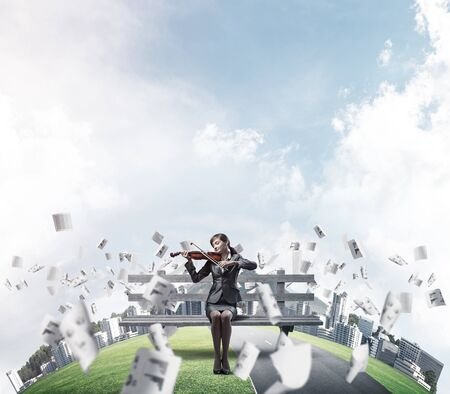 Young woman with violin sitting on wooden bench. Attractive businesslady playing violin. City panorama with round horizon of world and flying paperwork. Musician practicing and performing outdoors.