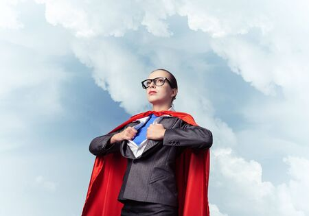 Portrait of business woman super heroine. Attractive young business lady in suit with red cloak on blue sky background. Successful and confident super woman in glasses ready for new challenges.
