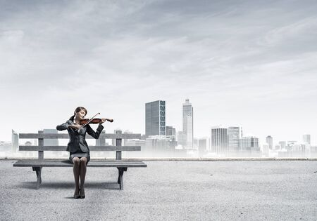 Young woman with violin sitting on wooden bench. Attractive businesslady playing violin on background modern cityline panorama with cloudy sky. Musician practicing and performing outdoors.