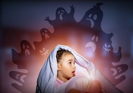 Excited girl hiding under blanket from imaginary ghosts. Scared kid sitting in his bed at home. Little girl afraid of fantasy monsters. Covered child in pajamas not sleep at night. Halloween holiday.