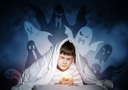 Young boy hiding under blanket from imaginary ghosts. Scared kid with closed eyes lying in his bed at home. Little boy afraid of fantasy monsters. Covered child in pajamas not sleep at night.