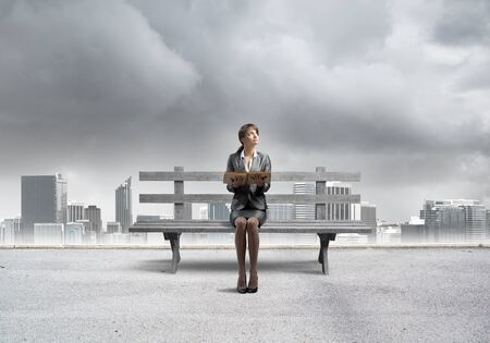Young woman holding open book and sitting on wooden bench outdoors. Beautiful girl in business suit looking up on background modern cityline panorama with storm sky. Business education and growth.