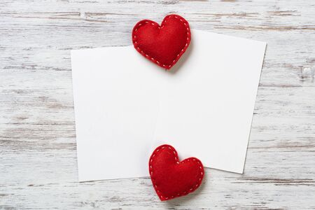 Blank sheets of paper and red love hearts on wooden table. View from above on romantic composition with copyspace. Declaration of love letter. White paper on wooden texture. Scrapbooking hobby