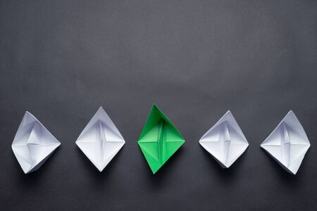 Row of paper ships on black background. Individual motivation and direction. Creative innovation and leadership. Flat lay green origami boat in group of white boats. Social marketing layout.