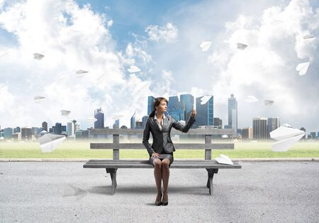 Business woman taking selfie photo or chatting with smartphone. Attractive girl using mobile phone on wooden bench. Mobile marketing and communication. Cityline panorama with flying paper planes.