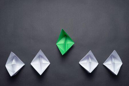 Bateau de chef d'origami origami vert à plat devant les autres bateaux. Rangée de navires en papier sur fond noir. Motivation et orientation individuelles. Innovation créative et leadership. Mise en page du marketing social. Banque d'images