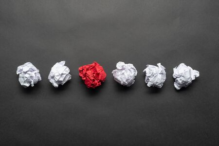 Crumpled red paper ball among white balls on black background. Extraordinary solution of problem. Business motivation with copy space. Unique and different experience. Idea generation and imagination