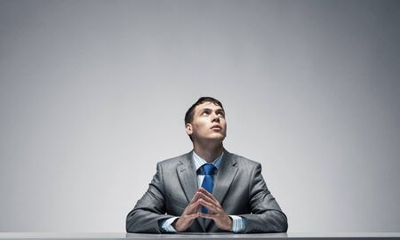 Serious man with folded hands looking upward. Young office worker or trainee sitting at desk. Portrait of guy wears business suit and tie on grey wall background. Businessman thinking about something