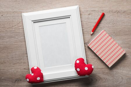 White photo frame small red hearts and pencil on wooden table