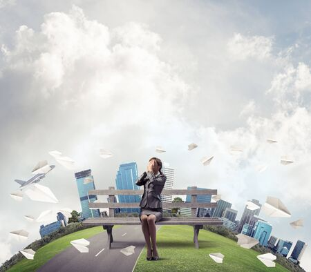Woman on wooden bench outdoors. Girl in business suit keeps hands on face for surprise. Hide from problems. Help and successful solutions. Panorama with round horizon of world and flying paper planes