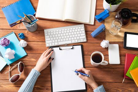 Businesswoman writing on white paper with pen at desk. Business research and education. Flat lay office workplace with female hands. Digital technology and coworking space. Female student taking notes