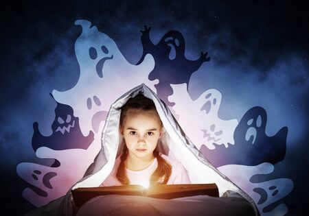Cute girl reading kids book in bed. Child with flashlight hiding under blanket. Smiling girl in pajamas and funny ghosts silhouettes back on night sky. Child reading magic fairy tales. Happy childhood