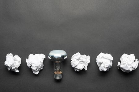 Lightbulb and crumpled white paper balls on black background. Successful solution of problem. Think outside the box. Business motivation with copy space. Genius idea among failing ideas metaphor. Imagens