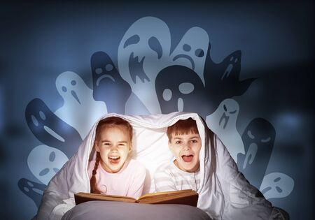 Happy little kids reading magic fairy tales in bed. Brother and sister together hiding under blanket. Little friends in pajamas with open big book and imaginary monsters on deep blue background. Stock Photo