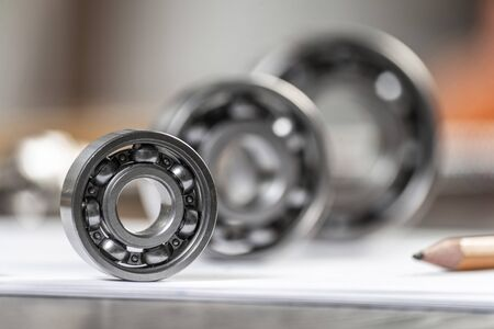 Three various ball bearings lying on paper sheet. Heavy industry engineering company. Automotive designing and manufacturing. Spare parts for machinery. Steel details for engine mechanisms.