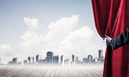 Human hand opens red velvet curtain to modern cityscape and cloudy sky 스톡 콘텐츠