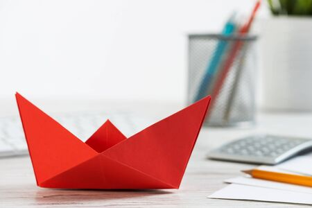Businessman workspace at office desk with red paper ship. Flat lay table with calculator, business reports and pen. Close up red origami boat. Creative and innovative solution for business.