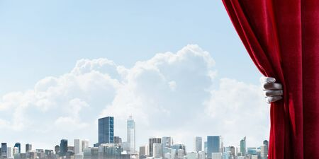 Human hand in glove opens red velvet curtain to modern cityscape 스톡 콘텐츠