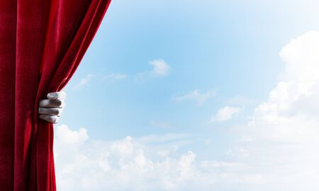 Human hand in glove opens red velvet curtain on blue sky background 스톡 콘텐츠