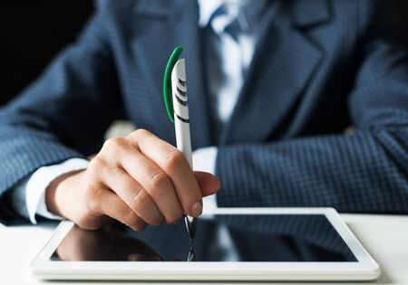 Man in business suit using digital tablet computer. Close-up of male hand holding pen and tablet device. Business man at workplace in office. Mobile smart device in business occupation. Stock fotó