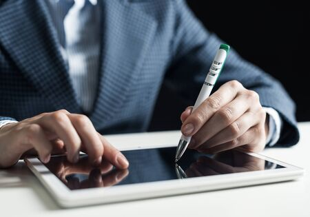 Man in business suit using tablet computer. Close-up of male hands holding pen and tablet gadget. Businessman at workplace in office. Mobile smart device in business occupation. Digital technology Stock fotó
