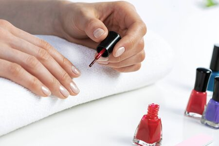 Woman giving herself elegant manicure at home. Closeup of beautiful female hand applying red nail polish at white table. Professional nail care and beautician procedure. Stylish nail art concept