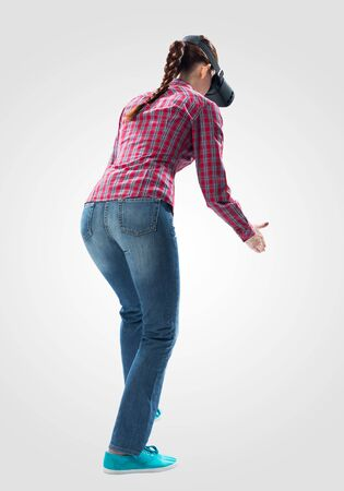 Young woman wearing VR headset and gesturing in air. Woman keep your hands in front of you as something holding. Interacts with cyberspace using gestures. Studio photo by girl against gray background