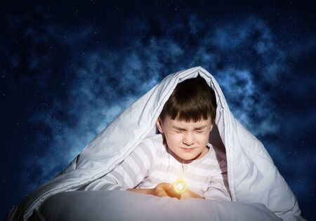 Frightened child with flashlight hiding under blanket. Scared kid with closed eyes lying in bed at home. Little boy can not sleep at night. Portrait of boy in pajamas on background of deep starry sky
