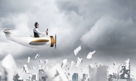 Business accounting and statistics concept with pilot. Aviator driving propeller plane above falling paper sheets with infographics. Man flying in small airplane above paperwork in dramatic cloudy sky
